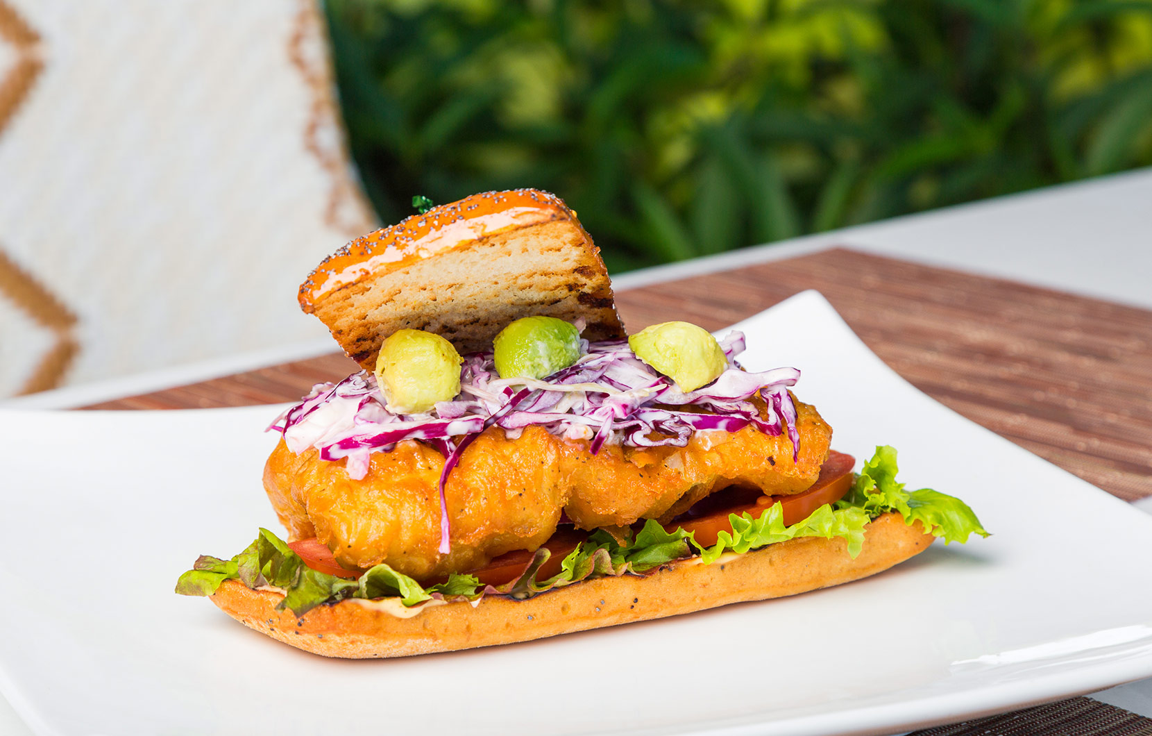 A flaky fish fillet topped with avocado pearls gives Chef Felipe's burger its character.