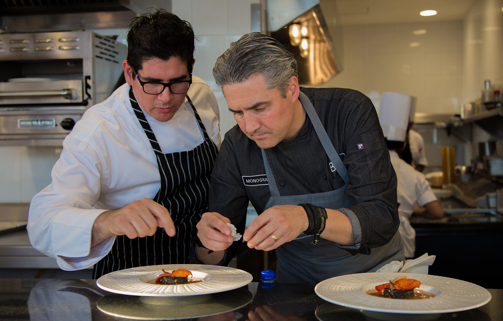 Chef Mikel Alonso works with Chef Enrique García of Epazote to artfully plate a dish.